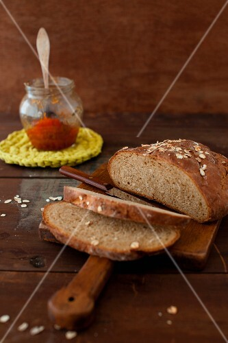 Partially Sliced Loaf of Oat Bread on a Cutting Board; Jar of Jam