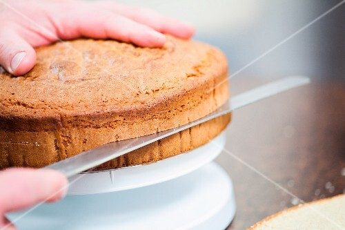 A sponge cake being sliced through the middle