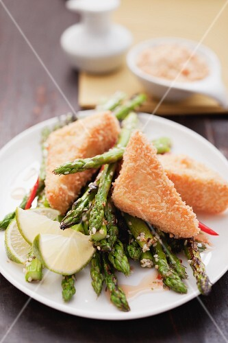 Breaded tofu on a bed of green asparagus with lime wedges