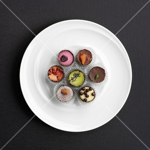 Assorted hand-made filled chocolates on a plate (view from above)