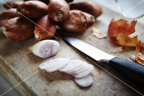 Whole and sliced shallots on a wooden board