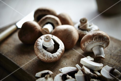 Button mushrooms on a wooden board