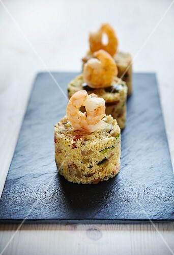 Couscous timbale with vegetables, bacon and prawns