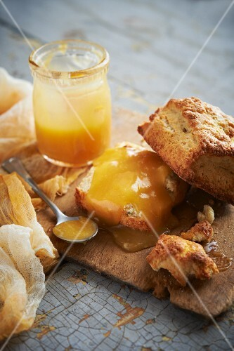 Lemon and buttermilk scones with lemon curd on a rustic wooden board