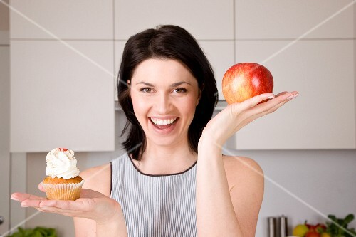 A woman holding up an apple and a cupcake