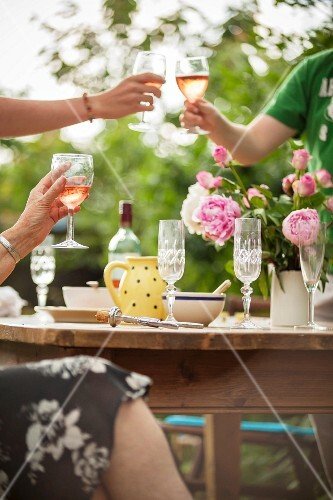 Friends clinking glasses of rosé wine in the garden