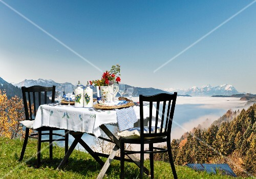 A table laid in the country house style, on an alpine meadow with a view over the Alps