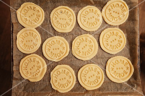 Unbaked biscuits stamped with 'home made' on a baking tray