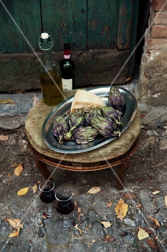 An Italian still life of artichokes, parmesan and red wine