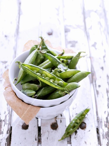 Fresh pea pods in a ceramic dish