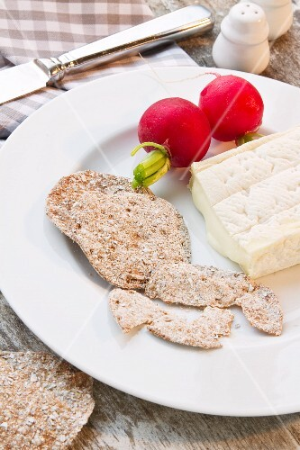 A snack of Camembert, rye crackers and radishes
