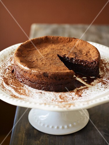 Chocolate cake dusted with cocoa powder, sliced
