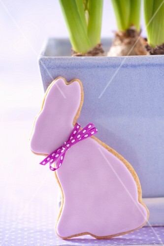 An Easter rabbit-shaped biscuit in front of a blue flowerpot