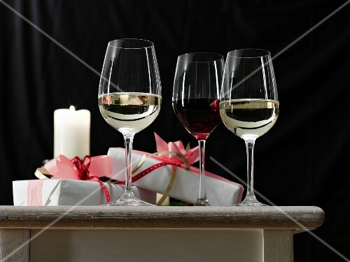 Red and white wine in glasses, alongside presents