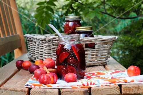 Rum-soaked plums in preserving jars on a table in the garden