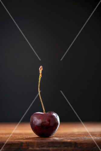 A cherry on a wooden table