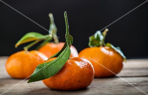 Four clementines with leaves on a wooden table