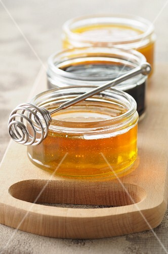 Three jars of honey on a chopping board