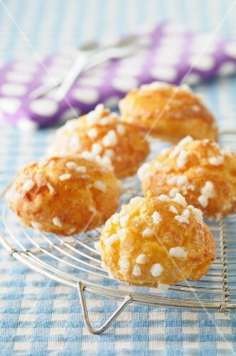 Chouquettes with sugar crystals on a cooling rack