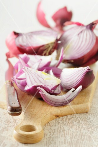 Red onions, partly sliced, on a chopping board