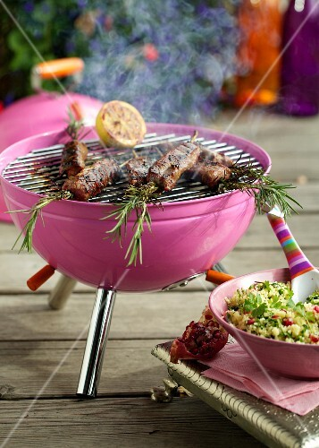 Lamb and rosemary kebabs on a pink barbecue, and tabbouleh