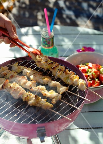 Chicken breast kebabs on the grill and a strawberry and spring onion salad