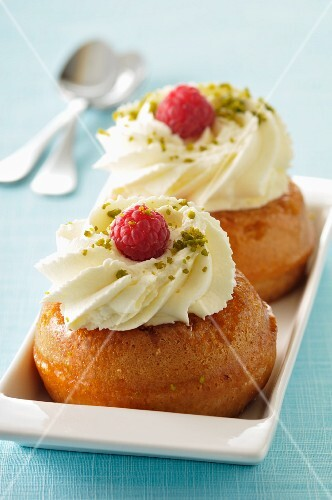 Rum baba with whipped cream and raspberries