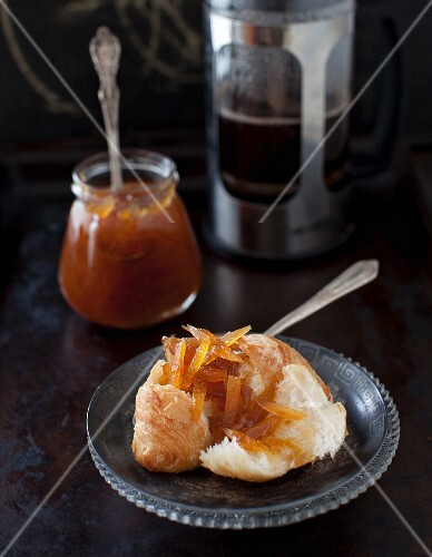 Grapefruit Jam on a Croissant; Jar of Grapefruit Jam in the Background
