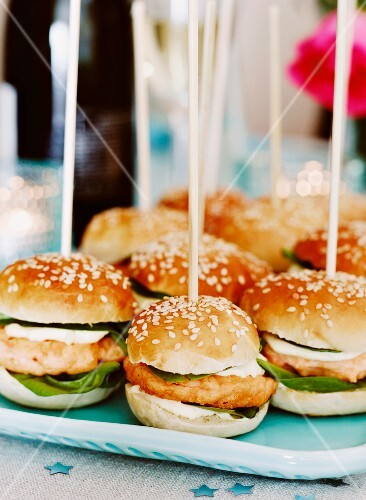 Salmon burgers in sesame seed buns on wooden skewers