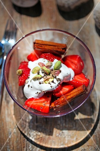 Strawberries with cream, pistachios and cinnamon sticks