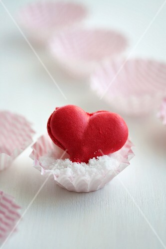 A heart-shaped strawberry macaroon in a paper case