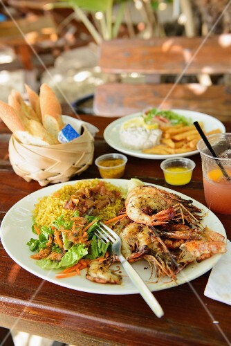Prawns with rice and salad on a restaurant table outdoors