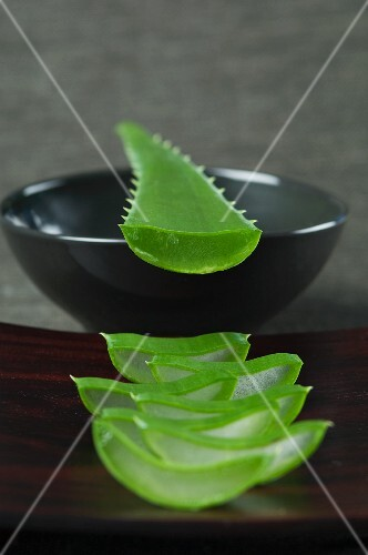 Sliced aloe vera shoots on a wooden board and on a bowl