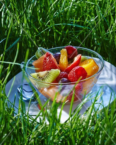 Fruit salad in a glass bowl in the grass