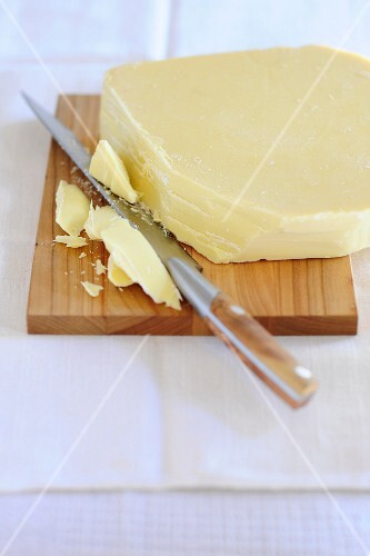 A slab of white chocolate on a chopping board with a few chunks cut