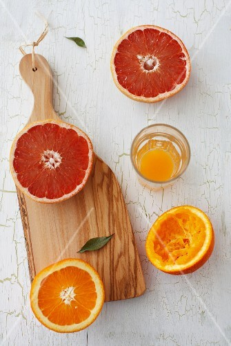 An orange and a grapefruit, cut in half, with orange juice squeezed from one orange half