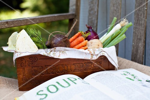 Fresh vegetables from the garden in a wooden crate, and an open cookbook
