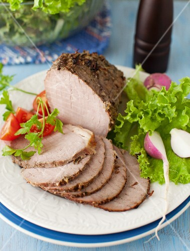 Partially Sliced Pork Roast on a Platter with Greens and Radishes