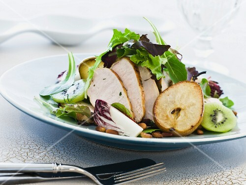 Green salad with chicken breast, kiwi, fried pear and toasted pine nuts