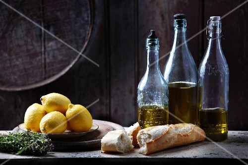 Lemon herbs and baguette with olive oil bottles