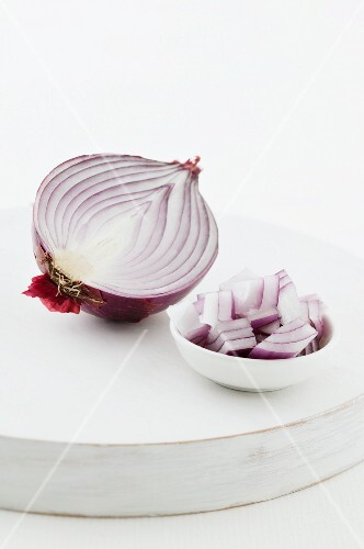 Half a red onion, and pieces of onion in a bowl