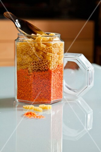 Dried pasta and red lentils in a storage jar with a scoop