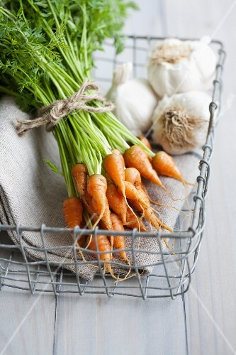 A bunch of baby carrots and garlic in a basket
