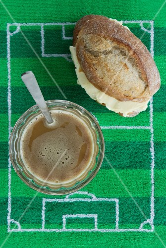 A breakfast of coffee and a bread roll (Brazil) with football-themed decoration