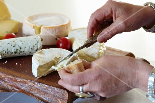 Slices of baguette being spread with Camembert, assorted types of cheese on a chopping board