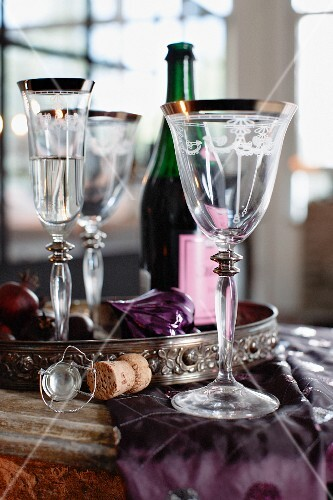 Champagne glass, wine glasses and wine bottle on a table set for Christmas