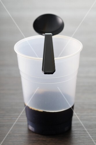 A plastic cup with a plastic spoon and the end of a cup of coffee