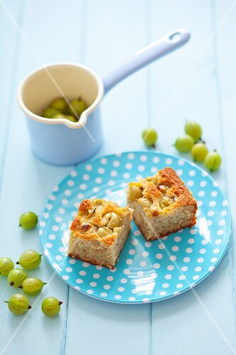 Two pieces of gooseberry cake on a spotted plate