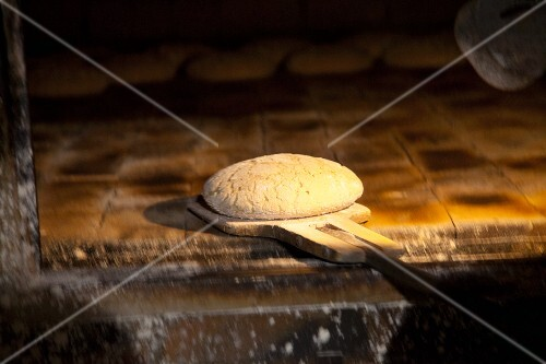 Unbaked bread on a wooden bread peel in the oven