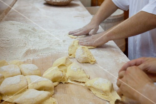 Bakers shaping bread rolls by hand